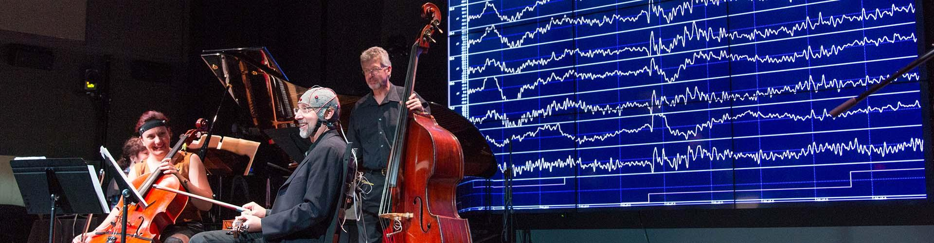 image of LIVELab research where musicians are performing with EEG caps with brain scans in the background