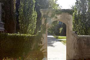 Image of famous arch on McMaster Campus surrounded by lush greenery and old architecture